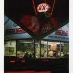 Exterior of Krispy Kreme store at night, with neon sign lit and the warm interior full of people beckoning customers inside.