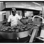 Black and white photo of an African American man wearing a Krispy Kreme hat stands behind a conveyer belt with Krispy Kreme doughnuts.