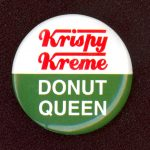 "Round button. Top half has a white background with ""Krispy Kreme"" in red; bottom half has green background with ""Donut Queen"" in white."