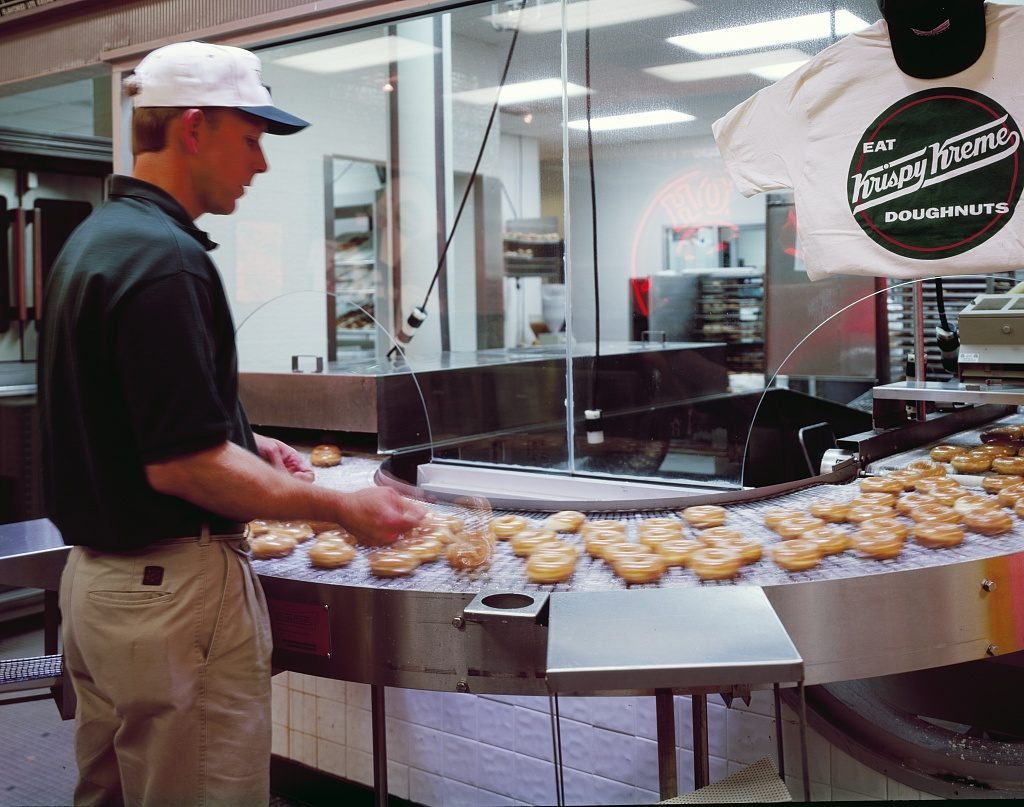 White male Krispy Kreme employee watches doughnuts on conveyer belt at the original Krispy Kreme store in Winston-Salem, NC.