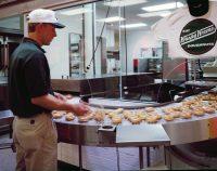 White male Krispy Kreme employee watches doughnuts on conveyer belt at the original Krispy Kreme store in Winston-Salem, NC.